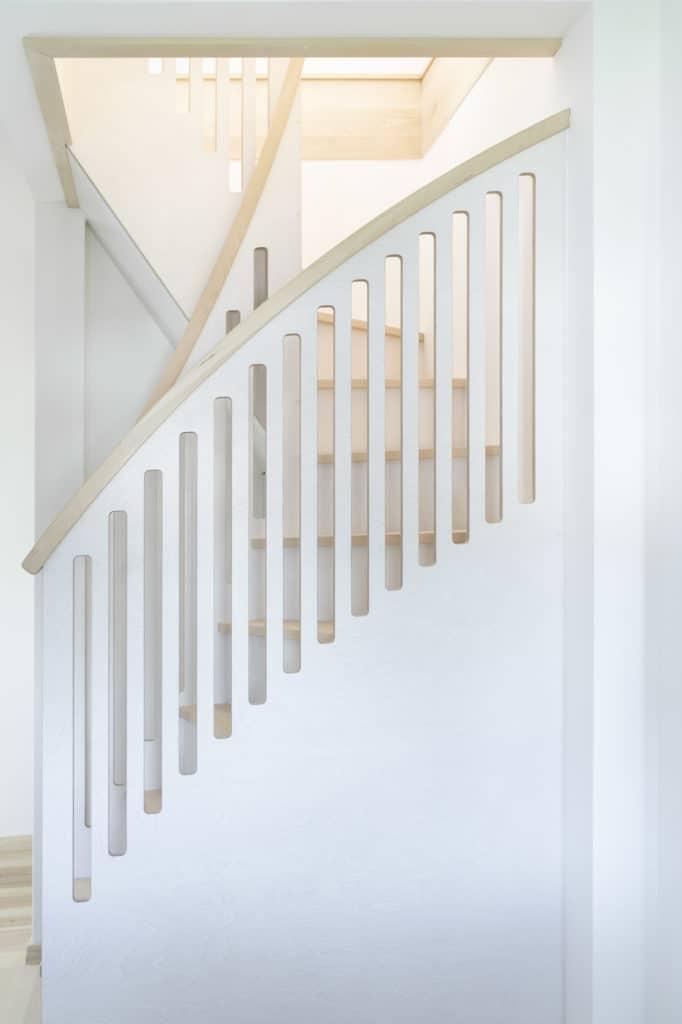 schlichte Raumspartreppe, eingepasst in ein sehr kleines Treppenloch aus Birke und weiß lasiertem Multiplex